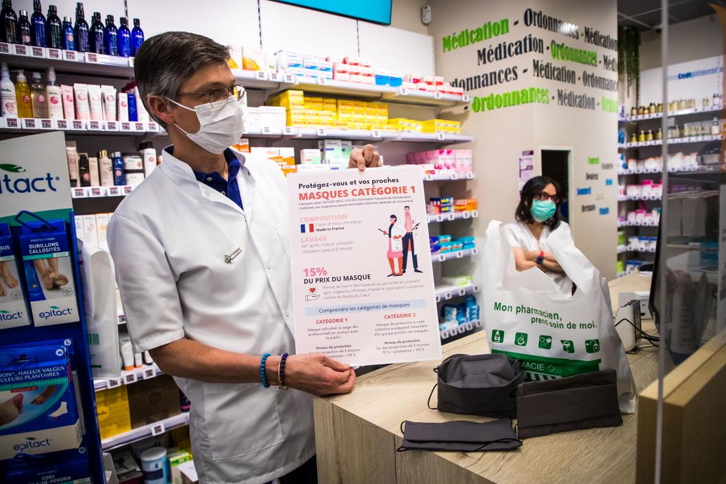 Фармацевт показывает инструкцию по обращению с новыми многоразовыми масками. Фото: EPA